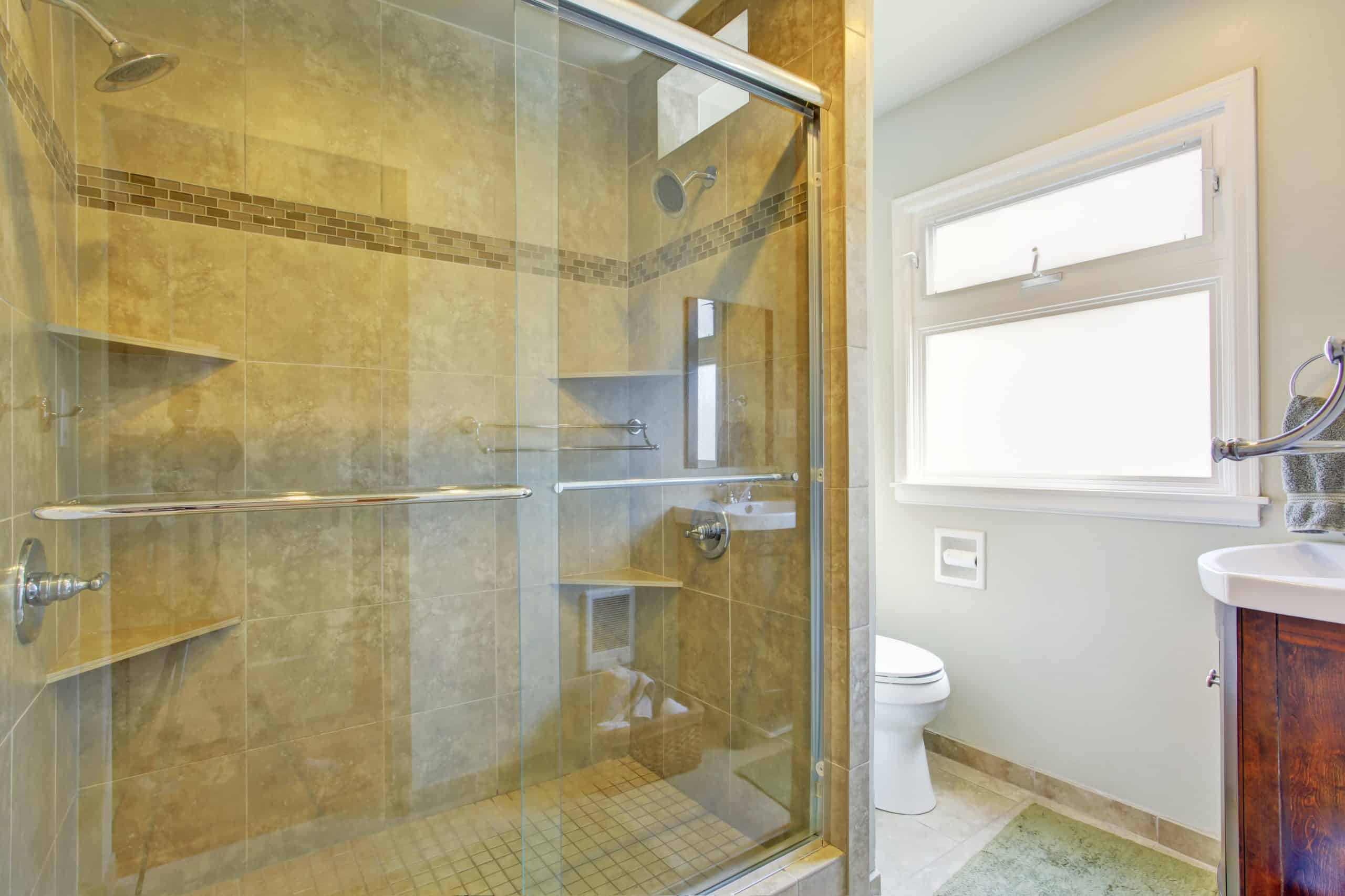 Aldora Fiesta glass shower doors see through to a tiled shower with shelves and hardware. A toilet, window and sink are seen to the right.