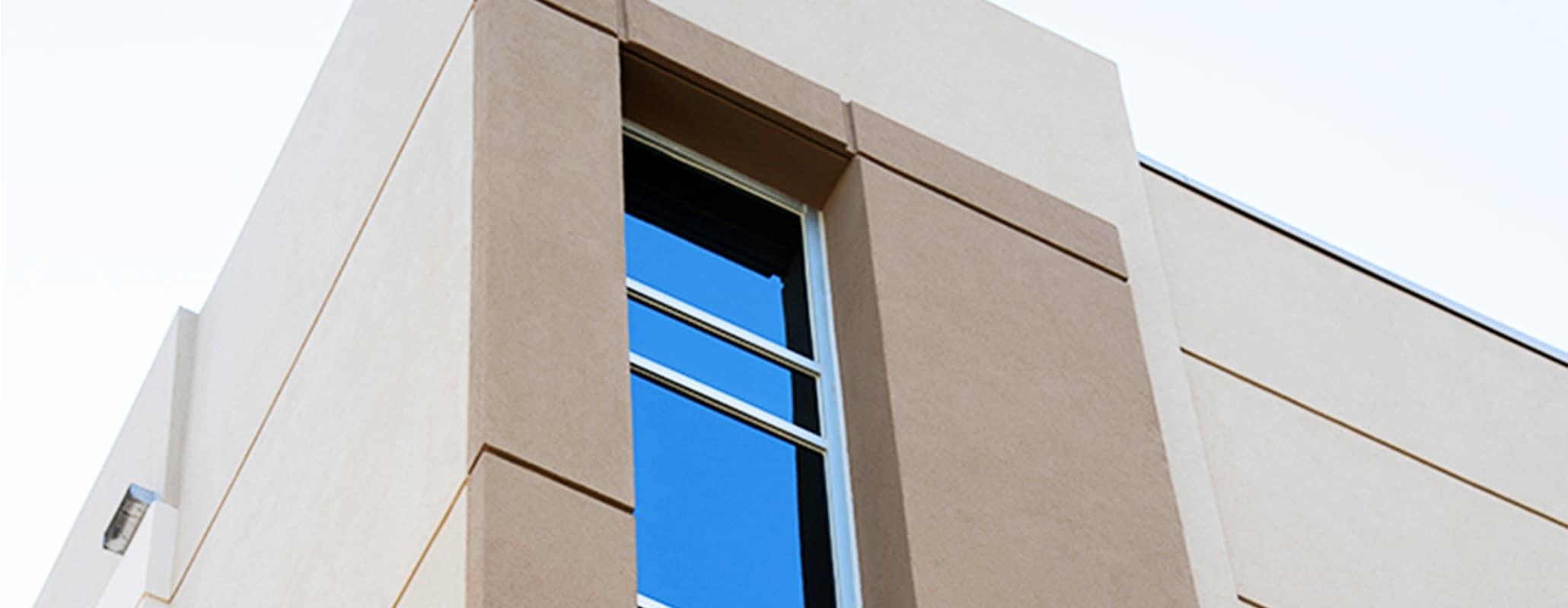 Aldora SMI-090 windows run down the corner of a commercial cement building
