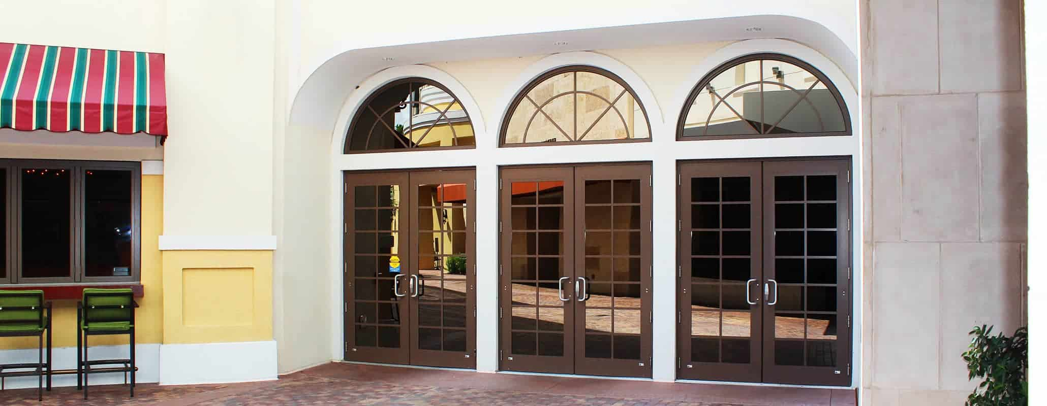 An exterior view of three Aldora impact glass doors with brick paved walkway in front and seating at the wall on the left.