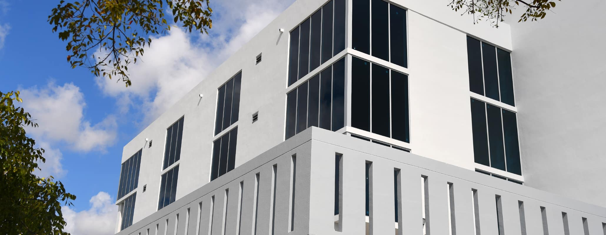 Modern concrete and glass large commercial building, stone balcony, glass curtain wall, RapidGlaze windows by Aldora.