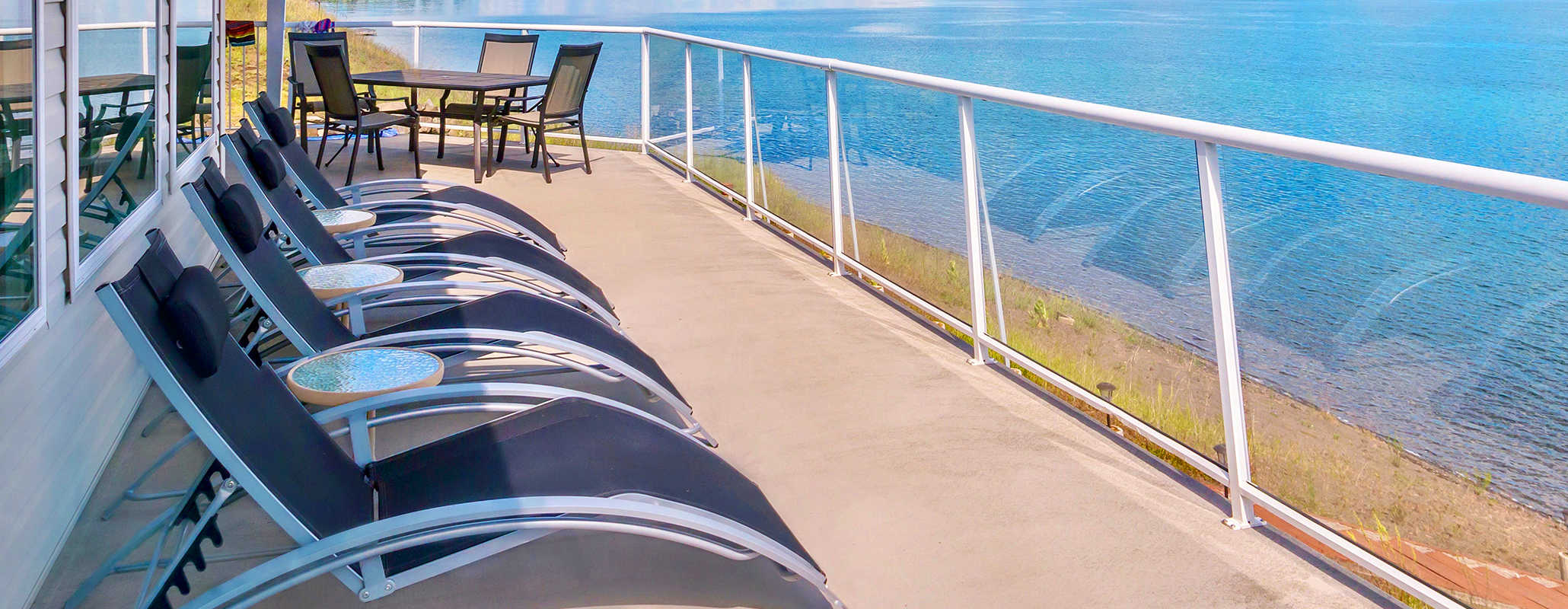 Lounge chairs, side tables and an outdoor table with chairs sit on a cement porch overlooking a beach. Aldora tempered glass acts as the railing on the porch.